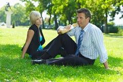 Geschäftsmann auf der Mittagspause, die im Gras sitzt Stockfotografie