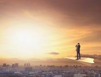 Geschäftsmann auf der Papierfläche, die durch binokulares zur städtischen Szene ausspioniert lizenzfreies stockfoto