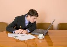 Geschäftsmann auf einem Arbeitsplatz mit dem Laptop Lizenzfreies Stockbild