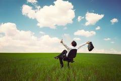 Geschäftsmann auf einem Gebiet mit einem blauen Himmel, der auf einem Büro Chai sitzt Stockbilder