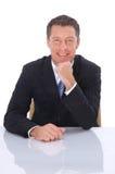 Geschäftsmann auf einem Schreibtisch Stockbild