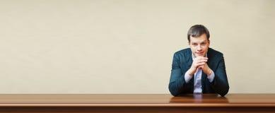 Geschäftsmann auf einem Schreibtisch Stockfotografie