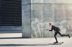 Geschäftsmann auf einem Skateboard, das sich vorwärts schnell bewegt Lizenzfreies Stockfoto