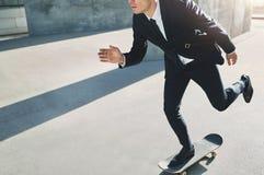 Geschäftsmann auf einem Skateboard, das zu einer Versammlung hetzt Lizenzfreie Stockfotos