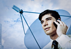 Geschäftsmann auf Handy mit Satellitenschüssel Stockfotos