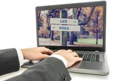 Geschäftsmann auf Laptop für Leben-und Arbeits-Konzept Stockbild