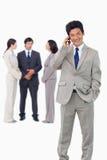 Geschäftsmann auf Mobiltelefon mit Team hinter ihm Lizenzfreies Stockfoto
