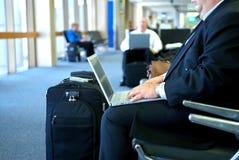 Geschäftsmann auf seinem Laptop im Flughafen Stockbilder