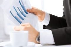 Geschäftsmann auf Sitzung Grafiken besprechend Lizenzfreie Stockfotografie