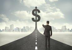 Geschäftsmann auf Straßenüberschrift in Richtung zu einem Dollarzeichen Lizenzfreies Stockfoto