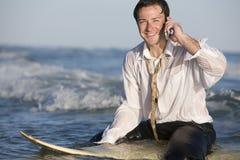 Geschäftsmann auf Surfbrett Stockfotografie