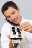 Geschäftsmann auf Telefon und der Konsultierung eines Kartenhalters Lizenzfreie Stockbilder