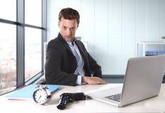 Geschäftsmann am Bürocomputertisch, der mit Gewehr und Wecker im Fristenkonzept aufwirft lizenzfreies stockbild