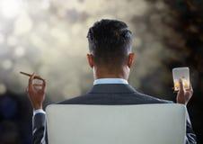 Geschäftsmann Back Sitting im Stuhl mit Zigarre und Getränkglas mit bokeh funkelnden Lichtern Lizenzfreie Stockbilder