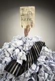Geschäftsmann begraben in zerknitterten Papieren Stockbild