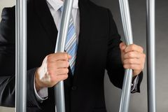 Geschäftsmann-Bending Bars Of-Gefängnis Stockbilder