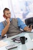 Geschäftsmann besetzt unter Verwendung des Telefons Stockfotos