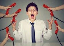 Geschäftsmann betont und nervös von zu vielen Arbeitsanrufen, die in der Verzweiflung schreien stockfoto