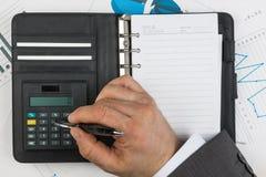 Geschäftsmann betrachtet auf dem Taschenrechner stockfoto