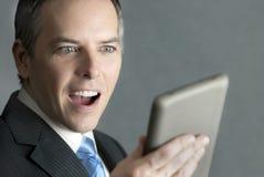 Geschäftsmann betrachtet Tablette mit erfreuter Überraschung Lizenzfreie Stockfotos
