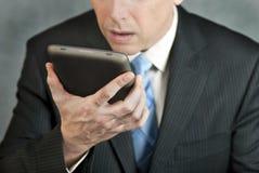 Geschäftsmann betrachtet Tablette mit Verzweiflung Stockfoto