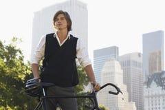 Geschäftsmann With Bicycle Standing im Stadt-Park Lizenzfreie Stockbilder