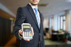 Geschäftsmann bietet Zahlungsanschluß für das Zahlen mit Kreditkarte an Stockbild