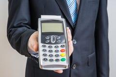 Geschäftsmann bietet Zahlungsanschluß für das Zahlen mit Kreditkarte an Lizenzfreie Stockbilder