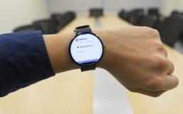 Geschäftsmann-Blick smartwatch am Konferenzzimmer-Showtagesordnungszeitplan wenn wo und Organisator Stockfotografie