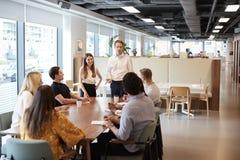 Geschäftsmann-And Businesswoman Addressing-Gruppe junge Kandidaten, die um Tabelle sitzen und auf Aufgabe bei graduiertem Recr zu lizenzfreie stockbilder