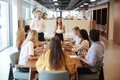 Geschäftsmann-And Businesswoman Addressing-Gruppe junge Kandidaten, die um Tabelle sitzen und auf Aufgabe bei graduiertem Recr zu stockbild