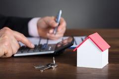 Geschäftsmann Calculating House Costs, das Taschenrechner verwendet Lizenzfreies Stockfoto
