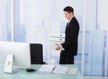 Geschäftsmann Carrying Stacked Binders am Schreibtisch Stockfotografie