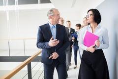 Geschäftsmann-Communicating With Female-Kollege beim an gehen lizenzfreies stockbild
