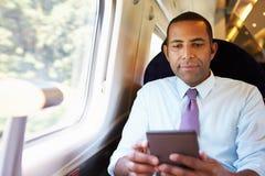 Geschäftsmann Commuting On Train, das ein Buch liest Lizenzfreie Stockbilder