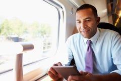 Geschäftsmann Commuting On Train, das ein Buch liest Stockfotos