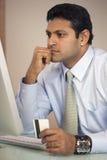 Geschäftsmann am Computer mit Kreditkarte Stockfoto