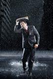 Geschäftsmann-Covering Head With-Mappe im Regen Stockbild
