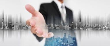 Geschäftsmann dehnen heraus Hand, mit Bau der Doppelbelichtungsstadt und des Immobilienstandorts und futuristische Stadt des Holo lizenzfreie stockfotografie
