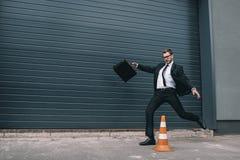 Geschäftsmann in den Brillen, die Aktenkoffer und Betrieb nahe Verkehrskegel halten Lizenzfreie Stockfotografie