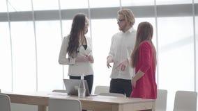 Geschäftsmann in den Gläsern gestikulierend beim Erklären seiner Idee zwei weiblichen Kollegen, die vor großem stehen stock video