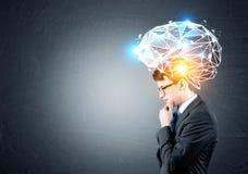 Geschäftsmann in den Gläsern mit großem Gehirnhologramm Stockfotos
