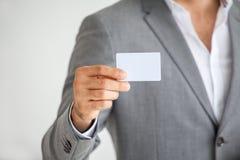 Geschäftsmann in den Klagen stellen dar oder, leeres weißes Kreditkartemodell halten lokalisiert auf weißem Hintergrund mit Besch stockbild
