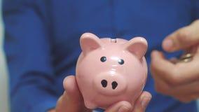 Geschäftsmann, den Mann Spareinlagen macht, setzt Münzen in ein Sparschwein ein Sparschweingeschäftskonzept Zeitlupevideo Stecken stock video footage