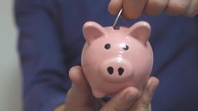 Geschäftsmann, den Mann Spareinlagen macht, setzt Münzen in ein Sparschwein ein Sparschweingeschäftskonzept Zeitlupevideo Stecken stock footage