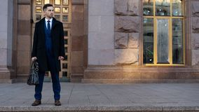 Geschäftsmann in den schwarzen Anzügen, die einen Aktenkoffer nahe einem Büro halten stockfotografie