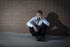 Geschäftsmann, den verlorener Job in der Krise verlor, die auf Stadtstraßenecke sitzt Stockfotos