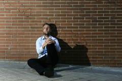 Geschäftsmann, den verlorener Job in der Krise verlor, die auf Stadtstraßenecke sitzt Stockbilder