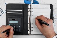 Geschäftsmann denkt auf dem Taschenrechner und schreibt lizenzfreie stockfotografie