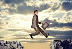 Geschäftsmann, der über Abgrund hüpft Lizenzfreies Stockbild